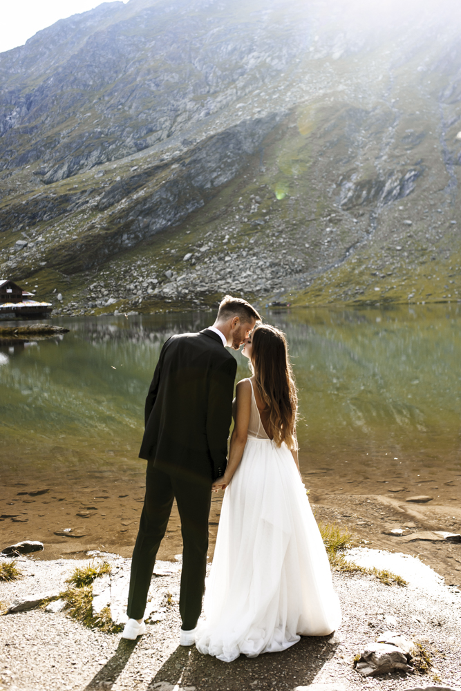 Full length of a amazing groom and bride kissing at the edge of
