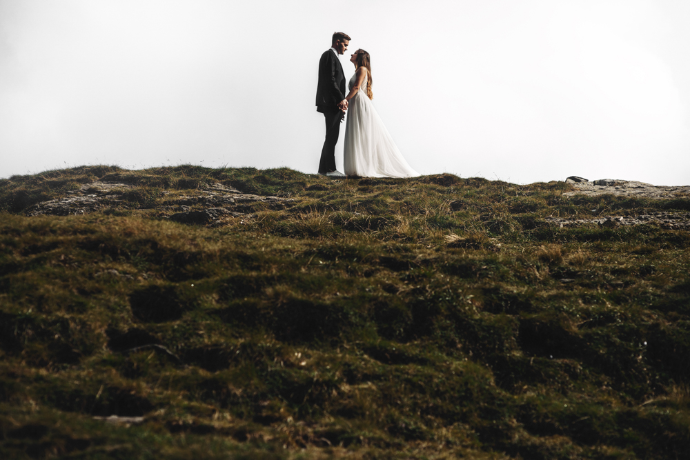 Full length of a amazing married couple embracing on a mountain.