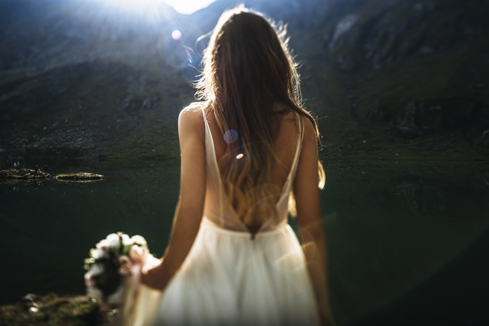 Unrecognizable back view of a young long haired bride walking ag