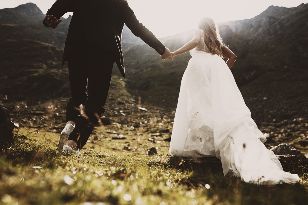 Crop view of legs of groom and bride running up on the mountains