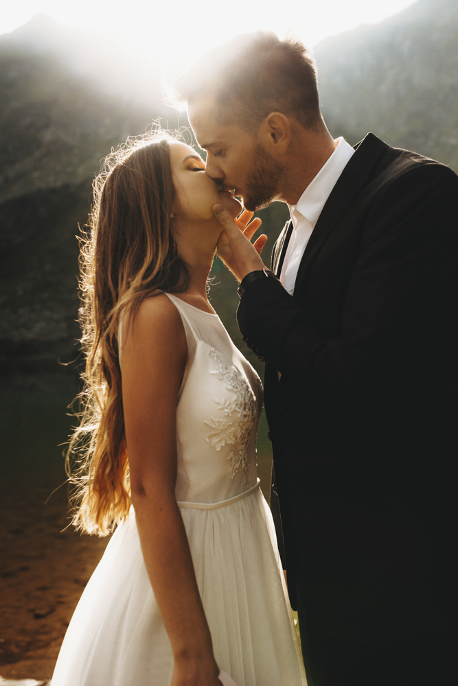 Side view portrait of a amazing wedding couple kissing against s