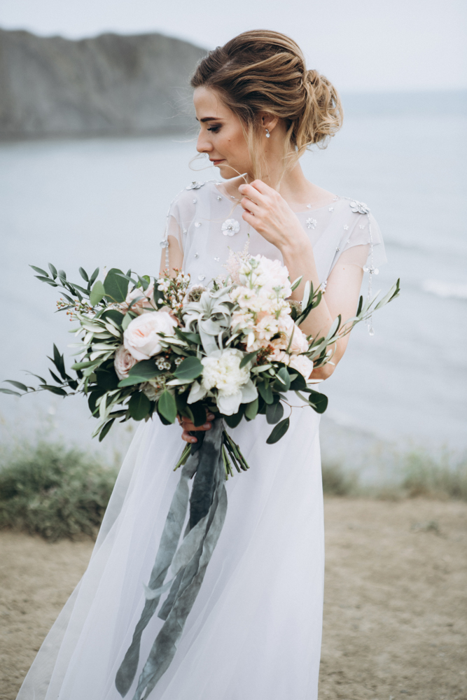 Pretty bride with wedding flowers by the sea